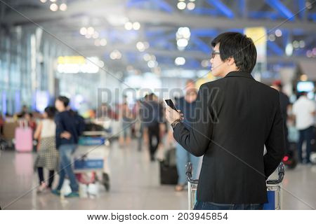 Young asian man with his suitcase luggage using smartphone while waiting for airline flight in the international airport terminal business travel and online check in concepts