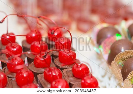 Macro picture of delicious dessert made with chocolates with cherry for woman party