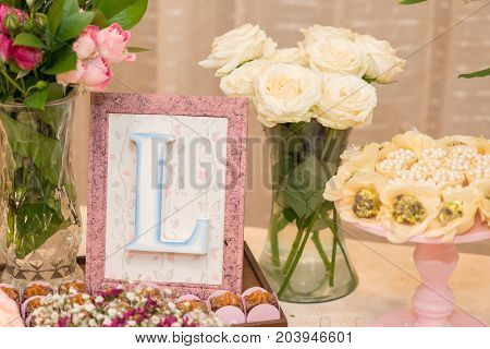 Front picture of letter L in a picture frames and milk candy dessert for woman party