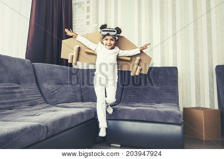 Child plays in the costume of the pilot and wants to fly in the sky