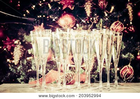 Filling Up Glasses For Party. Glasses Of Champagne With Christmas Tree Background And Sparkles. Holi