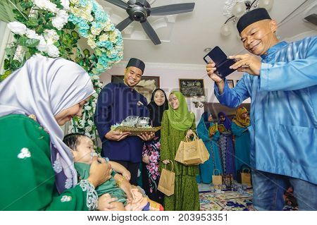 Labuan,Malaysia-July 30,2017:Man with smartphone taking picture of woman and baby during Aqiqah ceremony in Malay traditional ceremony at Labuan,Malaysia.
