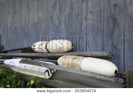 old wooden buoy floats laying against a wood shed