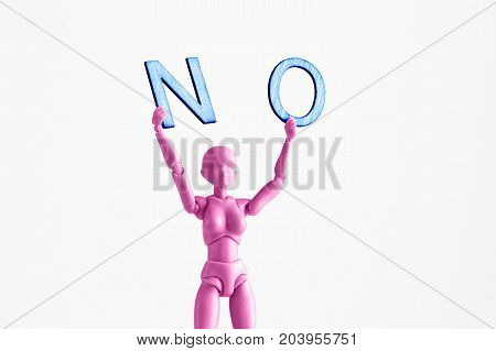 Pink female figurine closeup holding up the word NO. Isolated on white with copy space