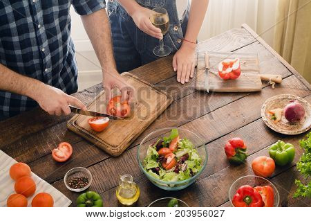 Husband is cooking dinner salad while his wife is drinking wine in home kitchen