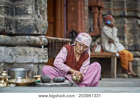 Naggar, India - July 17: Old Indian Woman Cleans The Dishes Out Of The Temple. Special Dishes Which