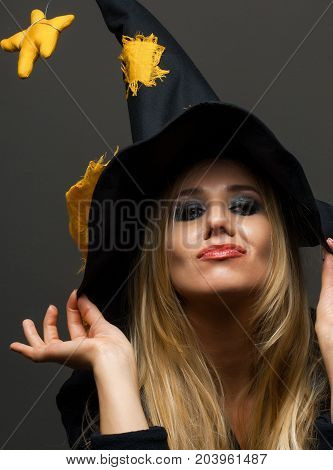 on halloween beautiful girl in a witch hat on a dark background
