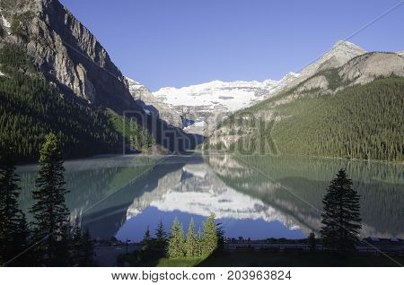 Early morning sun on Lake Louise with reflection and mist on the water