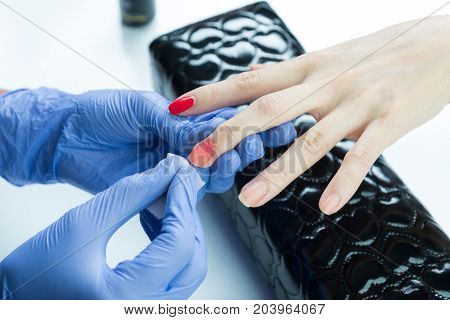Manicure and pedicure series: Manicurist removing nail polish