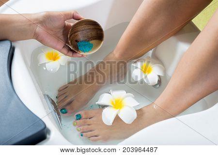 Manicure and pedicure series: Pedicurist pouring salt into pedicure bowl