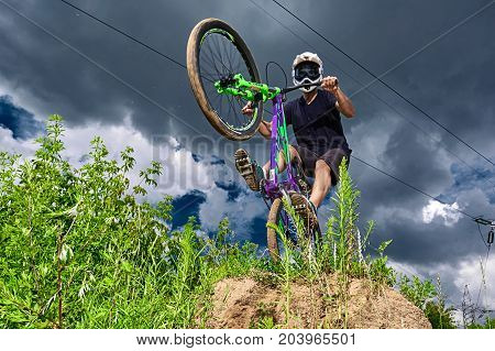 Moscow Russia - July 7 2017: Mountain bike cyclist doing wheelie stunt on a mtb bike. Biker riding extreme sport bicycle. Cool athlete cyclist on a bike. MTB biking.