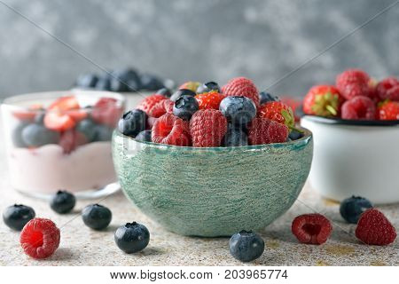 Fresh berries in a bowl on a brown background