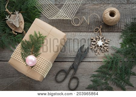 Preparation for Christmas holiday. Christmas Still life of giftbox decor twine fir tree twigs vintage scissors. Top view and copyspace. Flat lay.