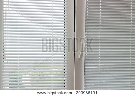 Fragment of thr modern tilt and turn plastic window with white Venetian blinds with manual control