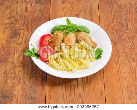 Braised meat roulades with filling from bread dried crusts and mushrooms tomato and spiral pasta decorated with basil and parsley twigs on a white dish on a surface of an old wooden planks
