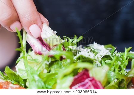 Woman eating green salad on plate by hand. Ruccola and cabbage with grated cheese, healthy nature food, dieting menu, close up picture