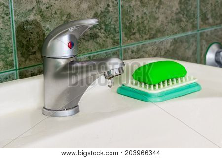 Single handle mixer tap mounted on a wash basin with drop of water on background of a wall with green tiles