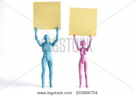 Male and female figurines holding up yellow paper notes above their heads isolated on white with copy space