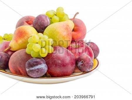 Fragment of the big yellow dish with several apples pears plums peaches and clusters of white grapes closeup on a white background