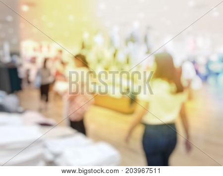 Blurred Image Of Happy Young Woman With White Shirt Shopping In A Shopping Mall, Over The Abstract B