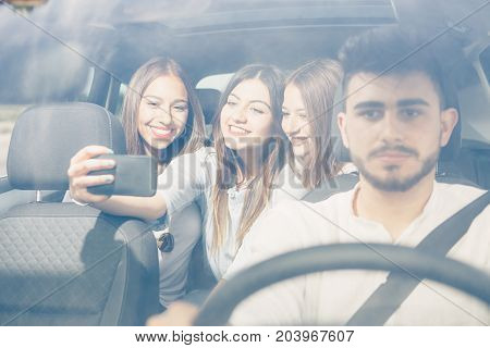 Group of friends making a selfie with a mobile phone sitting on the back of a car on a journey