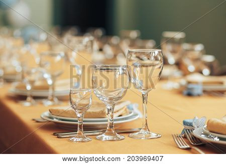 beautiful table setting in a restaurant. Dishesforks and glasses