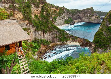 Happy family travel lifestyle. Mother with child sit on steps of traditional house on tree look at Atun beach Nusa Penida island. Popular travel destination on Bali holidays. Indonesian background.