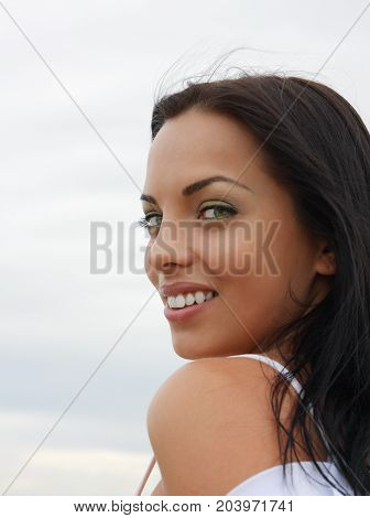 Beautiful green-eyed mulatto girl smiling looks into the camera outdoors