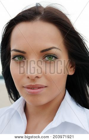 Beautiful green-eyed mulatto girl looks into the camera outdoors