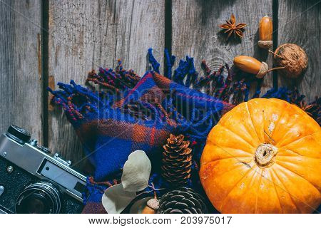 Autumn background pumpkin acorns leaves plaid plaid film camera on wooden boards. Top view copy space.