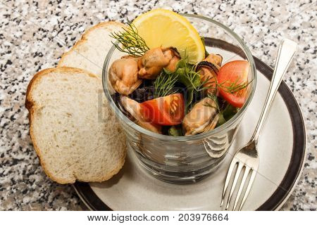 fresh mussel salad in a glass with bread
