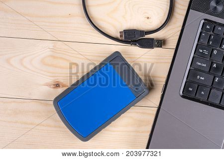 Flat Lay Above External Hard Disc By Lap Top Computer On The Wooden Table With Copy Space