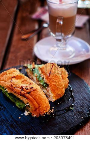 Cut croissant with salmon and greens and a glass of coffee for breakfast.