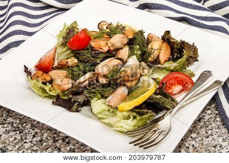 fresh mussel salad with tomato on a white plate