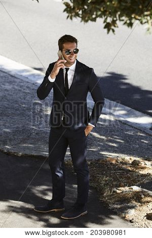Business dude in shades takes a call on sidewalk