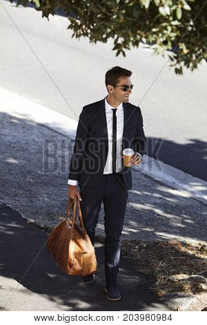 Businessman with bag walking on sidewalk smiling