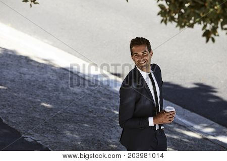 Happy businessman in suit smiling to camera