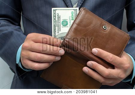 Savings. Poverty. Pay the debts. The man in the suit pulls out one hundred last dollars from wallet.