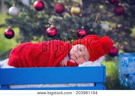 Portrait Of Newborn Baby In Santa Clothes Lying Under Christmas Tree