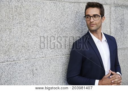 Thoughtful businessman in suit and glasses looking away