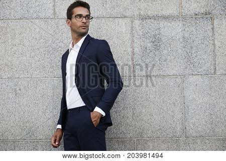 Seriously handsome businessman with glasses looking over shoulder