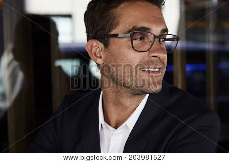 Smartly dressed man in jacket and glasses looking away