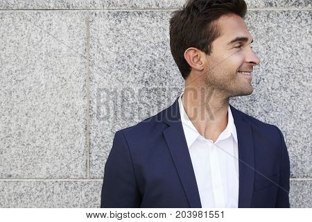 Smiling business guy in suit and shirt looking away
