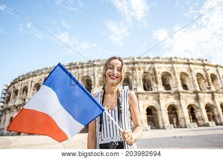 Young woman tourist standing with french flag in front of the ancient amphitheatre in the old town of Nimes during the sunny morning in France