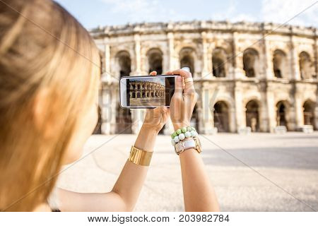 Young woman tourist photographing with smartphone ancient amphitheatre in the old town of Nimes during the sunny morning in France