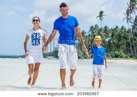 Family of three - father with his child having fun at the beach