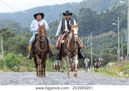 May 27 2017 Sangolqui Ecuador: cowboys arriving on horse back on a country road to a rural rodeo in the Andes