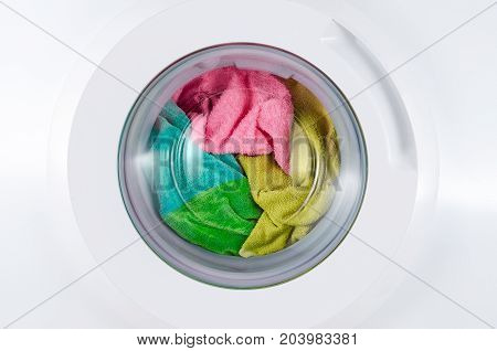 washing machine with color clothes closeup, closed