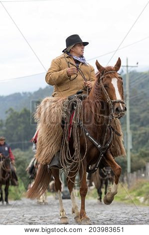 May 27 2017 Sangolqui Ecuador: cowboy on horse back wearing chaps riding to a rural rodeo in the Andes