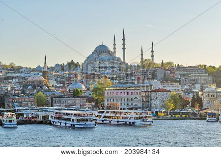Istanbul Turkey - April 25 2017: Istanbul city view from Galata Bridge overlooking the Golden Horn with Eminonu (Turyol) ferry terminal and Suleymaniye Mosque before sunset